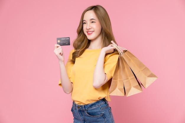 Mooie aziatische vrouw die bruine blanco ambachtelijke papieren boodschappentassen vasthoudt en creditcard op roze achtergrond toont.