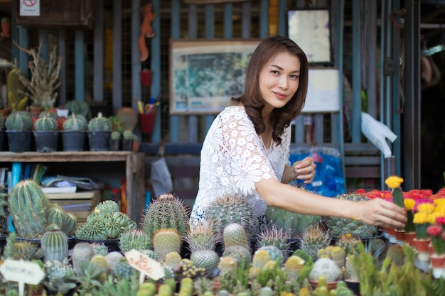 Mooie aziatische vrouw die cactus in bloemenwinkel selecteert, levensstijl van moderne huisvrouw.