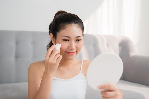 Mooie aziatische vrouw die cosmetische spons op het gezicht gebruikt en thuis in de spiegel kijkt