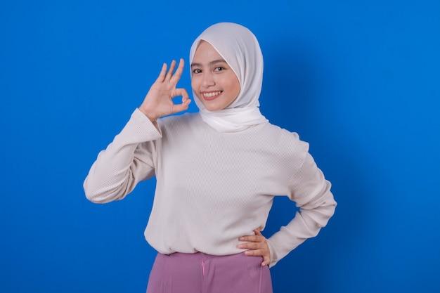 Mooie aziatische vrouw die de lange witte uitdrukking van de t-shirtglimlach met haar hand gebruikt