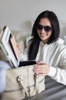 Mooie aziatische vrouw die documenten tablet pc notitieblok dagboek in handtas zet klaar om vakantie te reizen