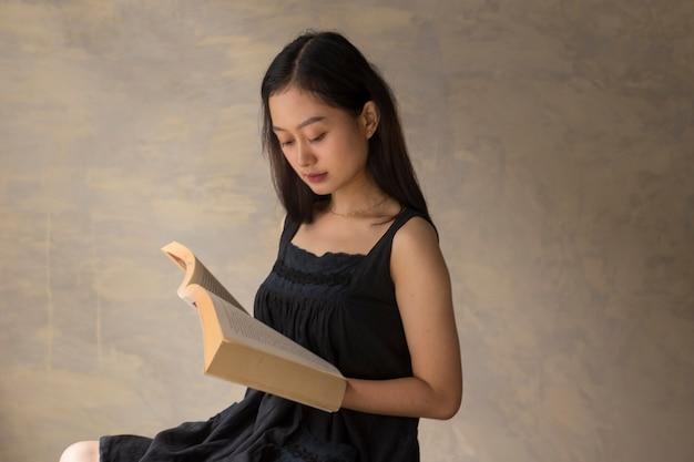 Mooie aziatische vrouw die een boek leest