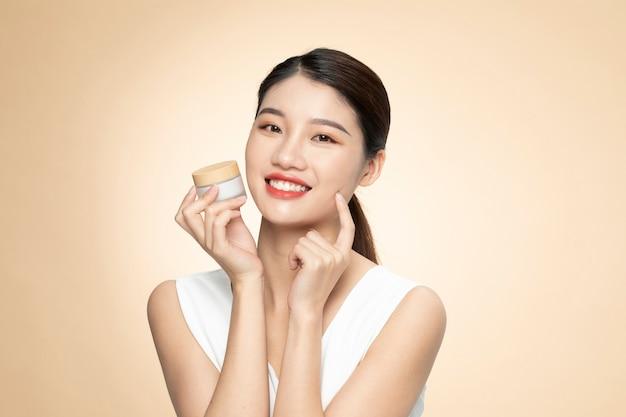 Mooie aziatische vrouw die een fles product op een oranje achtergrond houdt