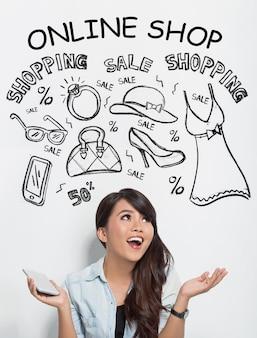 Mooie aziatische vrouw die een handphone houdt terwijl het voorstellen over online het winkelen