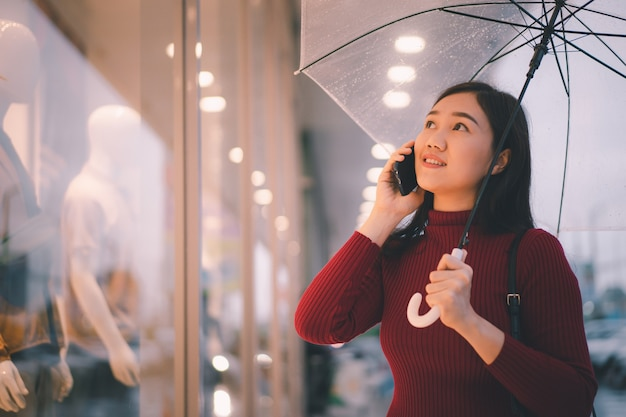 Mooie aziatische vrouw die een lange straat loopt en een smartphone gebruikt terwijl het regent,