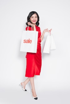 Mooie aziatische vrouw die een rode jurk draagt met een boodschappentas die zich over wit bevindt.