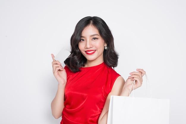 Mooie aziatische vrouw die een rode jurk draagt met een boodschappentas en een creditcard vasthoudt die over wit staat.