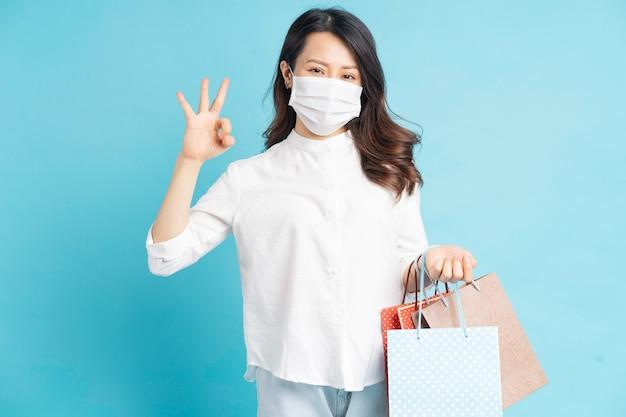 Mooie aziatische vrouw die een wit masker draagt dat een boodschappentas draagt en met de hand ok maakt