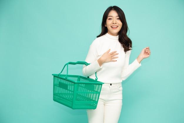 Mooie aziatische vrouw die en het winkelen mand glimlacht houdt die op lichtgroene muur wordt geïsoleerd