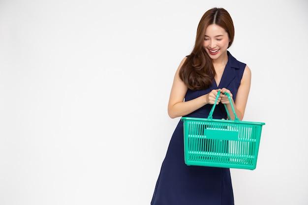 Mooie aziatische vrouw die en het winkelen mand glimlacht houdt die op witte muur wordt geïsoleerd