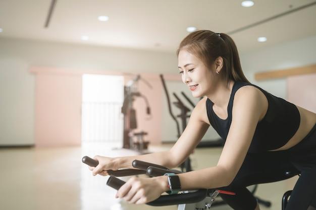 Mooie aziatische vrouw die en op de draaiende fiets berijdt uitoefent bij de geschiktheidsgymnastiek.
