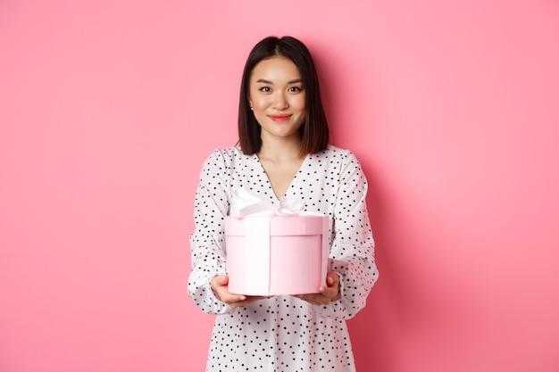 Mooie aziatische vrouw die fijne feestdagen wenst en je een cadeau geeft in een schattige doos die tegen een roze achtergr...