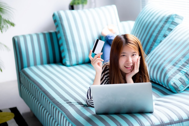 Mooie aziatische vrouw die gebruikerscreditcard met laptop ligt