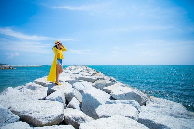 Mooie aziatische vrouw die gele kleren draagt die zich op overzees strand tegen het licht van de middagzon bevinden