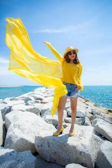 Mooie aziatische vrouw die gele kleren dragen die zich op overzees strand tegen middagzonlicht bevinden