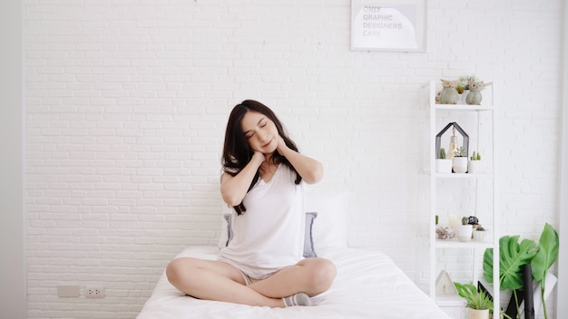 Mooie aziatische vrouw die haar lichaam uitrekt nadat zij in haar slaapkamer thuis ontwaakt.