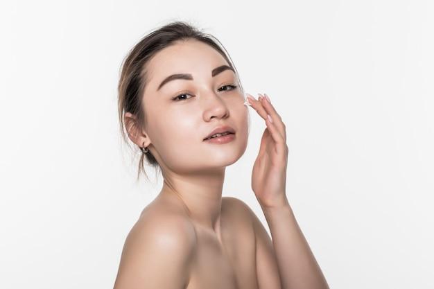 Mooie aziatische vrouw die haar schoonheidsgezicht met reinigend schuim op haar handen voor huidzorg wast die op witte muur wordt geïsoleerd