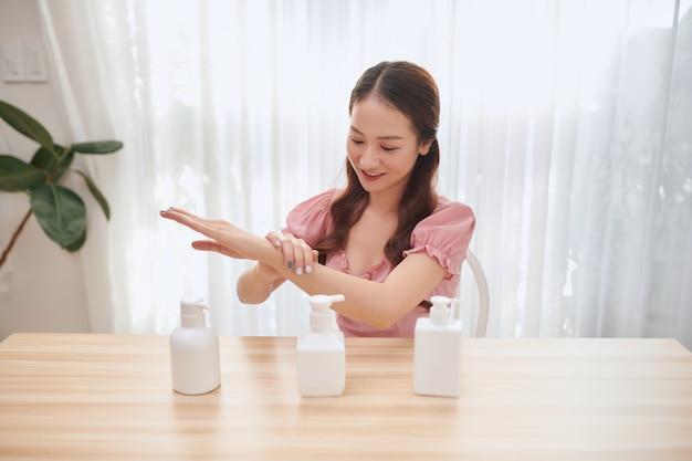 Mooie aziatische vrouw die handdesinfecterend middel thuis gebruikt.