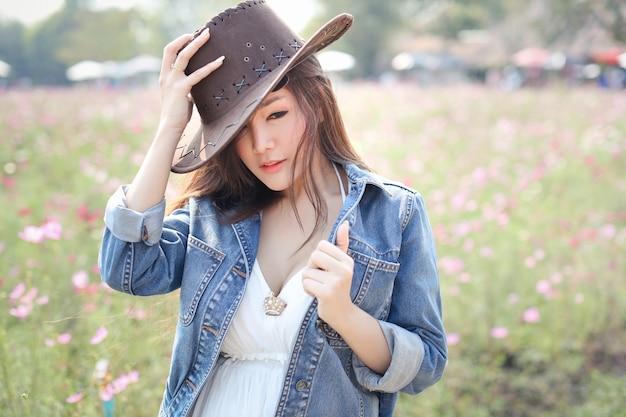 Mooie aziatische vrouw die het dragen van blauwe jean die zich in de natuur tussen de kosmos velden met vreedzame bloemen