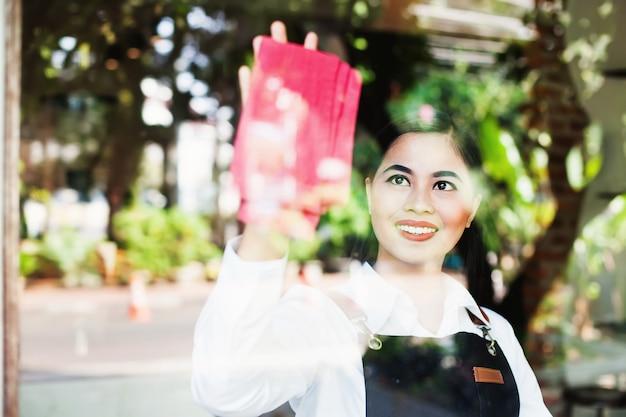 Mooie aziatische vrouw die het glas met de doek schoonmaakt