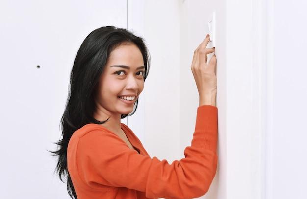 Mooie aziatische vrouw die het licht met muurschakelaar uitzet