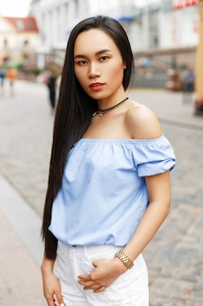 Mooie aziatische vrouw die in de stad loopt