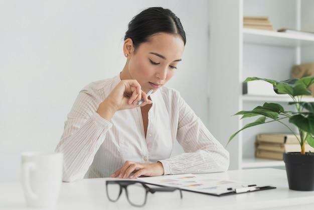 Mooie aziatische vrouw die in het bureau denkt