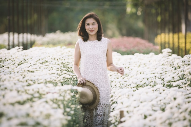 Mooie aziatische vrouw die in tropische bloementuin loopt en glimlacht met een geluksmanier met warm zonlicht van de achtergrond.
