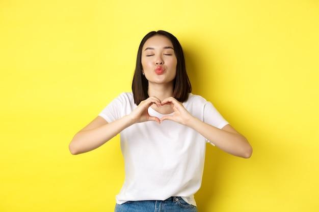 Mooie aziatische vrouw die laat zien dat ik van je hou hartgebaar, glimlachend in de camera, staande tegen een gele achtergrond. concept van valentijnsdag en romantiek