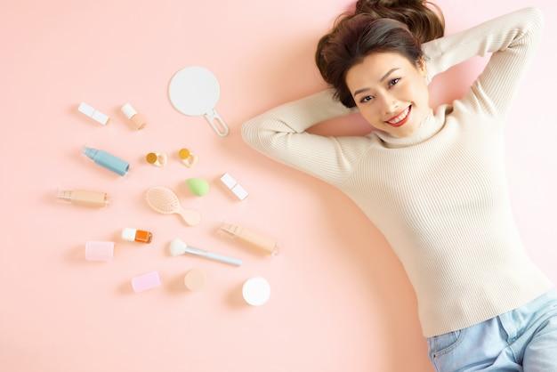 Mooie aziatische vrouw die lacht terwijl ze op een roze vloer ligt met haar cosmetische make-uptools