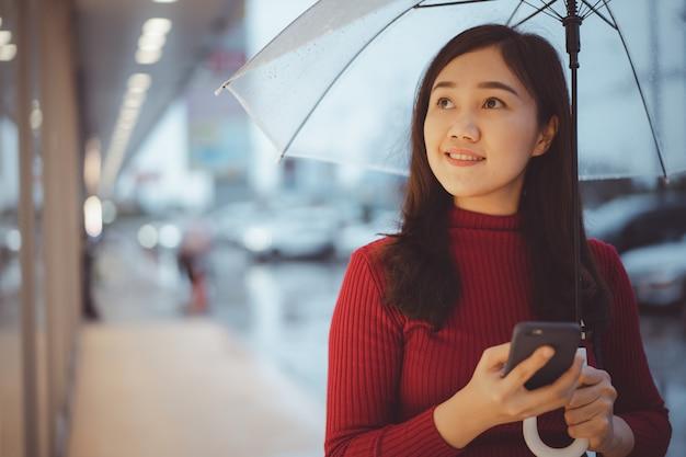 Mooie aziatische vrouw die lang door de straat loopt en een smartphone gebruikt terwijl het regent, vrouw die naar de winkel in het centrum kijkt.