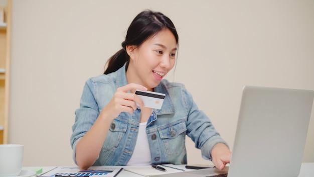 Mooie aziatische vrouw die laptop met behulp van die online winkelend door creditcard kopen terwijl draag toevallige zitting op bureau in woonkamer thuis.