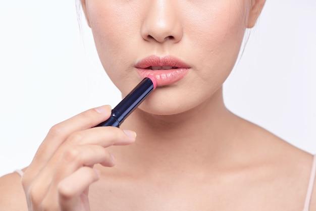 Mooie aziatische vrouw die lippenstift toepast, op wit wordt geïsoleerd