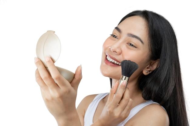 Mooie aziatische vrouw die make-up aanbrengt met borstel