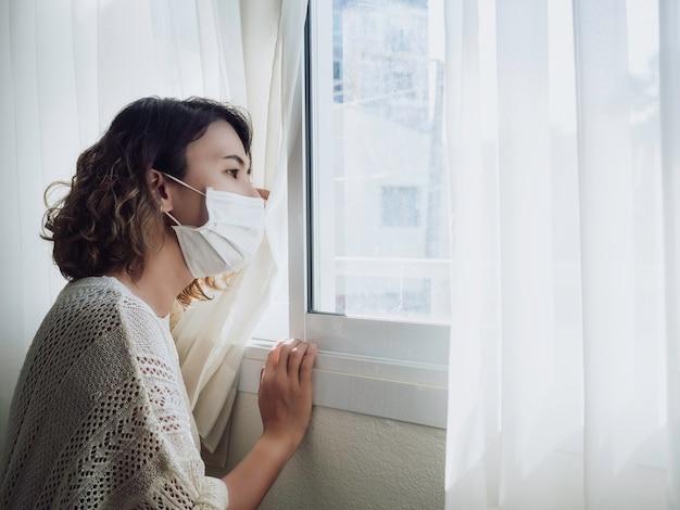 Mooie aziatische vrouw die medisch gezichtsmasker draagt dat uit het venster kijkt