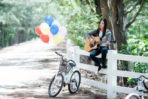 Mooie aziatische vrouw die met akoestische gitaar glimlacht