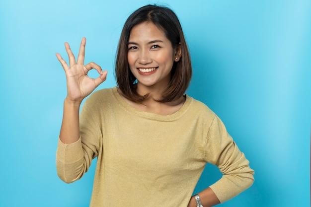 Mooie aziatische vrouw die met hand ok teken glimlacht