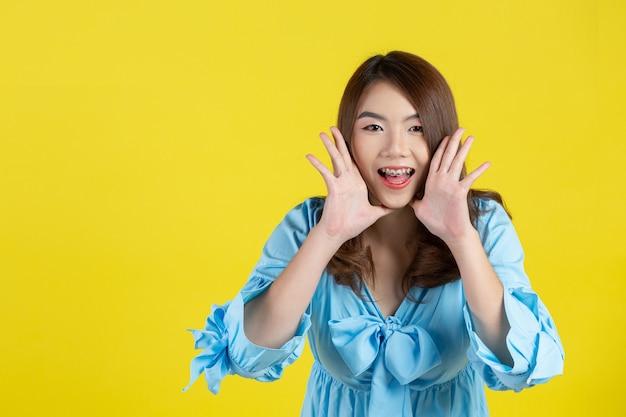 Mooie aziatische vrouw die met handen schreeuwt die rond mond op gele muur tot een kom wordt gevormd
