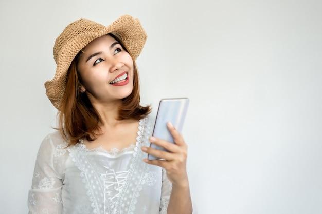 Mooie aziatische vrouw die met slimme telefoon glimlacht