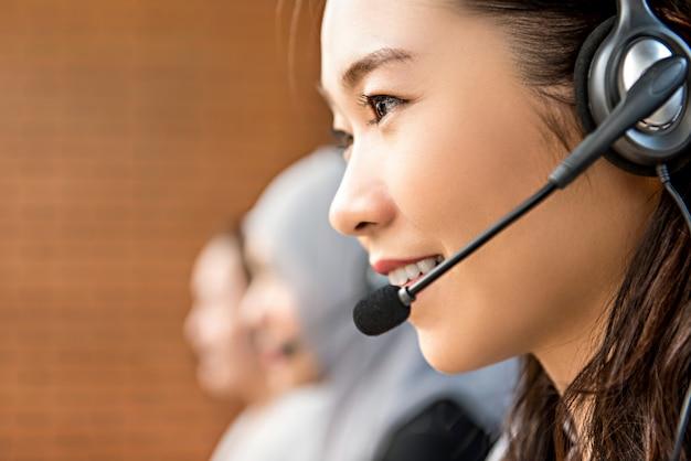 Mooie aziatische vrouw die microfoonhoofdtelefoon draagt die in call centre werkt