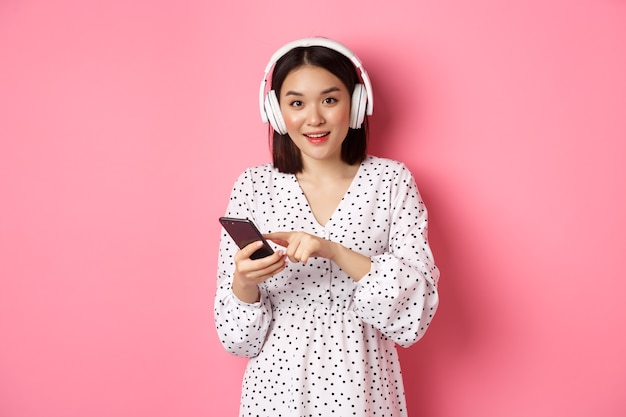 Mooie aziatische vrouw die muziek luistert in een koptelefoon, mobiele telefoon gebruikt, gelukkig lacht naar de camera, staande over roze achtergrond