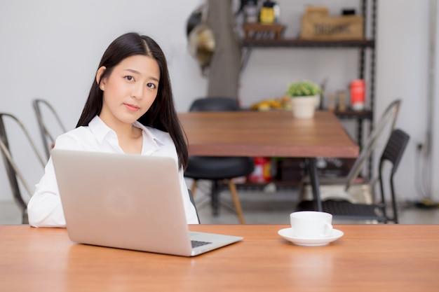 Mooie aziatische vrouw die online aan laptopzitting bij koffiewinkel werkt