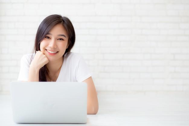 Mooie aziatische vrouw die online laptop werkt