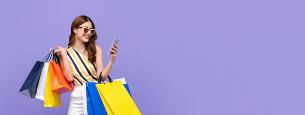Mooie aziatische vrouw die online met mobiele telefoon winkelt