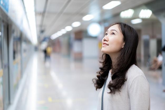 Mooie aziatische vrouw die op een trein in metro (ondergronds) platform wachten