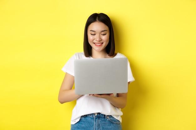 Mooie aziatische vrouw die op laptop werkt, gelukkig op het scherm kijkt, staande over gele achtergrond.
