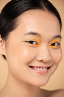 Mooie aziatische vrouw die oranje oogschaduw draagt