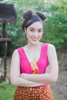 Mooie aziatische vrouw die plastic waterkanon in traditioneel kostuum van het speelwater van thailand in songkran-festival houden