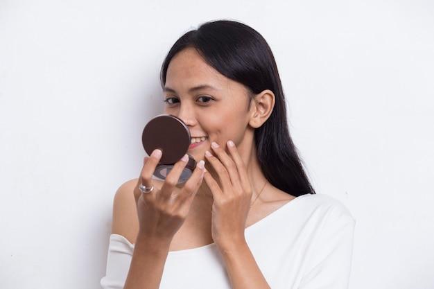 Mooie aziatische vrouw die poeder aanbrengt bij make-up van cosmetica geïsoleerd op een witte achtergrond