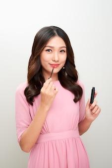 Mooie aziatische vrouw die rode lipgloss houdt en het toepast